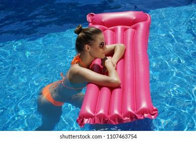 Young woman in bikini holding air mattress in the swimming pool
