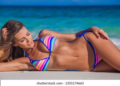 Young woman in bikini laying by tropical sea