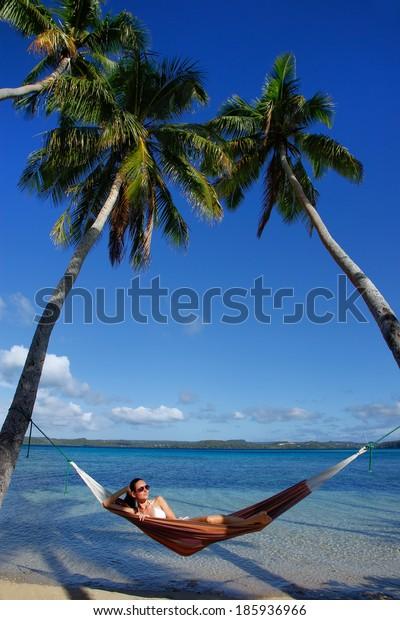 Young woman in bikini laying in a hammock between palm trees, Ofu island, Vavau group, Tonga