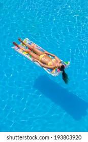 Young woman in bikini in a lilo in the swimming pool
