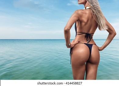 Young woman in bikini looking at sea water on the beach of tropical resort. Rear view
