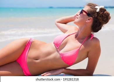 young woman in bikini lying on tropical beach