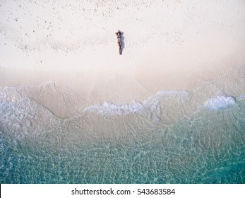 Young woman in a bikini lying on the back on the sand near the waves of blue sea. Top view. Kai island, Andaman Sea, Phuket, Thailand. Aerial Shooting.