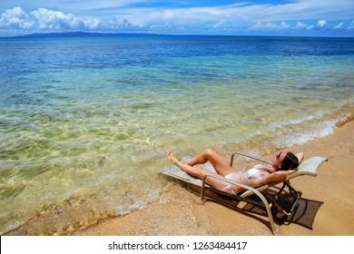 Young woman in bikini lying in a sun chair on Taveuni Island, Fiji. Taveuni is the third largest island in Fiji.