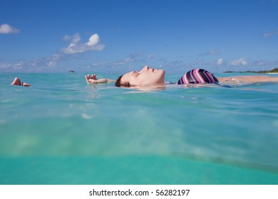 A young woman in a bikini lying upon the water surface with her eyes closed