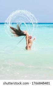 Young woman in bikini make water splash and having fun