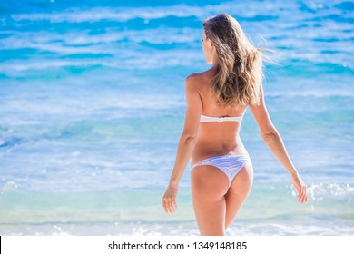 Young woman in bikini on tropical beach walking to sea. Summer vacation and tanning concept.
