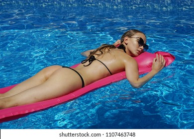 Young woman in bikini relaxing and swimming on air mattress in the pool