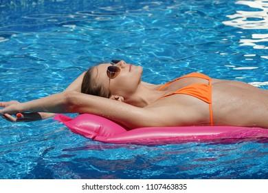 Young woman in bikini relaxing and swimming on air mattress in the pool