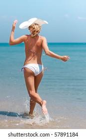 Young woman in bikini running on the beach