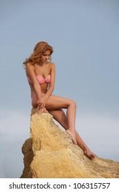 Young woman in bikini sitting on the yellow rock