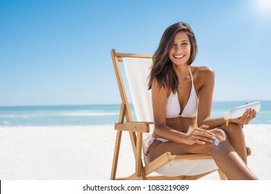 Young woman in bikini sitting on deckchair and applying sun lotion on leg. Portrait of smiling latin girl applying sun screen on body at beach with copy space. Beautiful woman enjoying sunbathing.