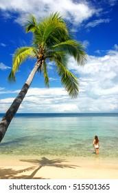 Young woman in bikini standing in clear water, Nananu-i-Ra island, Fiji, South Pacific