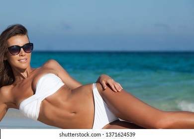 Young woman in bikini and sunglasses laying by tropical sea