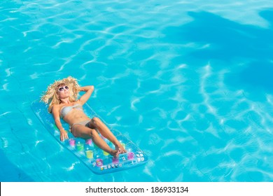 Young woman in bikini wearing a straw hat in the swimming pool
