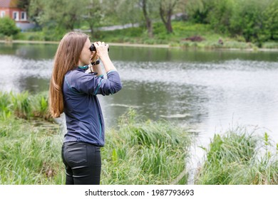 Young woman birdwatcher looking for the birds on the river or lake. Image with copy space