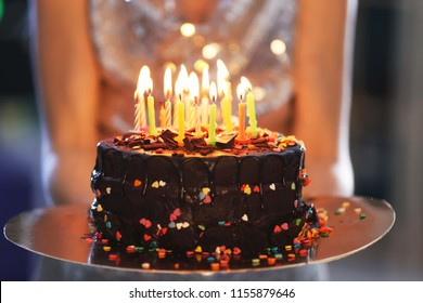 Young woman with birthday cake, closeup