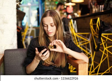 young woman with a bitcoin and smartphone sits in a cafe.