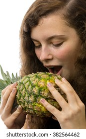 A young woman bites into a pineapple
