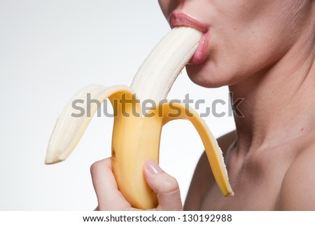 Young woman biting banana isolated on white