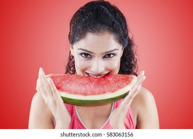 Young woman biting a big slice of sweet watermelon while smiling and looking at the camera on the red background