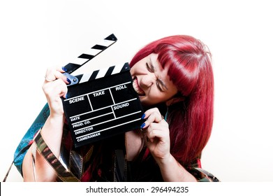 Young woman biting movie clapper board with 35 mm filmstrip and white background