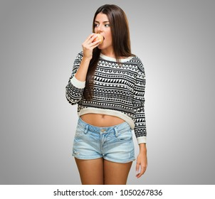 Young Woman Bitting an Apple against a grey background