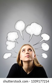 Young woman in black and blank speech bubbles over her head. Girl solving a problem.