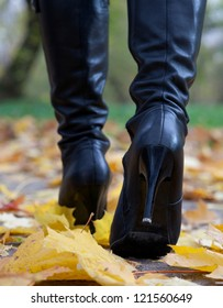Young woman in black boots on heels in the autumn