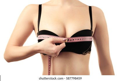 Young woman in black bra with measuring tape on white background, closeup