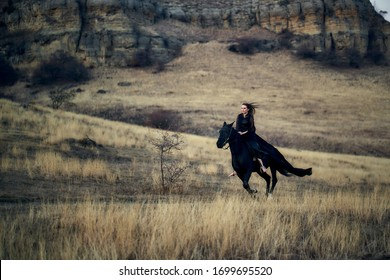 A young woman in a black cloak galloping on her black horse along a mountain trail. In the background mountains and rocks