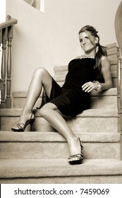 Young woman in a black cocktail dress and crystal necklace and bracelet sitting on the steps of a curves staircase