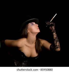 The young woman in a black corset smoke cigarette and looks up