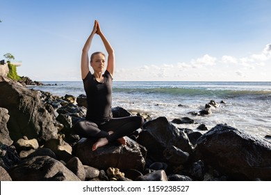 Young woman in black doing her yoga on asian rock beach sitting sukhasana pose. Healhy lifestyle, happy vacation in tropics, morning exercises.