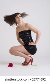 Young woman with black dress does hair flip with flower on ground