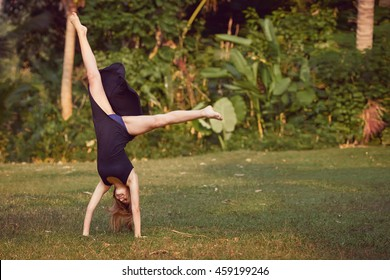 Young woman in black dress doing cartwheel on the grass