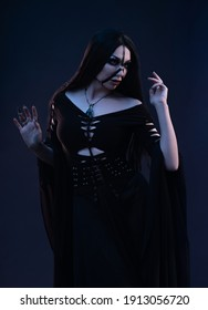 Young woman in black dress in Gothic style posing in studio