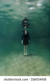 Young woman in black dress standing on sand underwater