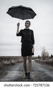 Young woman in a black dress with the umbrella