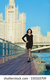 A young woman in a black dress walking along the waterfront with her hand on the belt