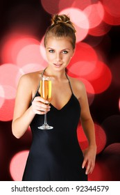 Young woman in black elegant dress holding goblet with champagne