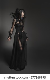 Young woman in black fantasy costume with feathers on dark background