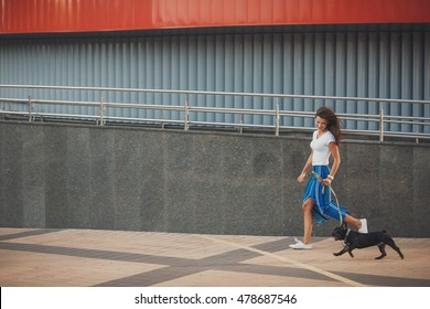 Young woman with black french bulldog puppy walking at the street