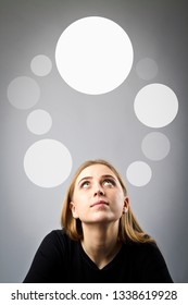 Young woman in black and gray bubbles. Doubts and hesitation.
