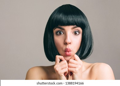 Young woman with black hair posing on camera. Amazed emotional model with bob haircut. Holding pieces of hair between fingers. Lips together. Beautiful brunette isolated on light studio background.