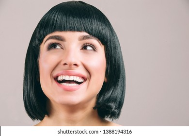 Young woman with black hair posing on camera. Brunette bob haircut. Smiling and looking up to left. Cheerful young woman. Isolated on light background.