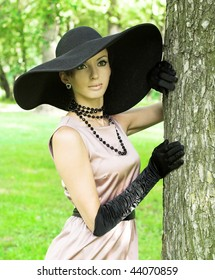 Young woman in black hat walking in the park. Retro style.