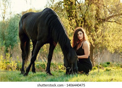 Young woman with black horse in evening sunset light. Outdoor photography with fashion model girl. Russia, Ufa. May 2019