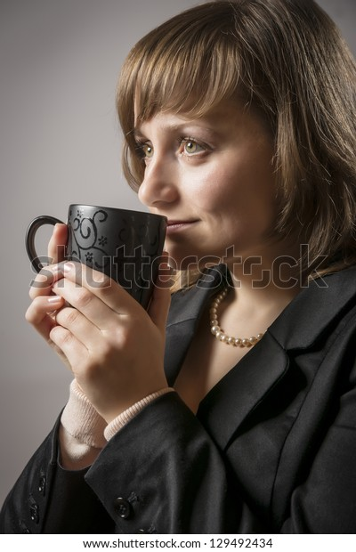 Young woman in black jacket drinking from a cup