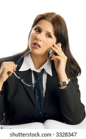 a young woman in black jacket and white shirt and a tie sitting down behind an office table and talking by phone